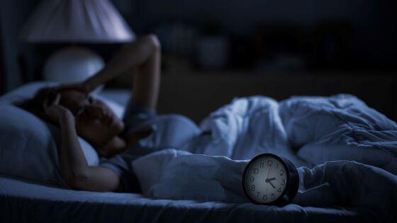 kvinne som ligger i sengen og sliter med å få sove. Vekkerklokke i forgrunnen.
