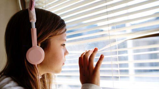Jente som titter ut gjennom vinduet.