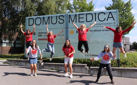 Studenter som hopper foran et skilt