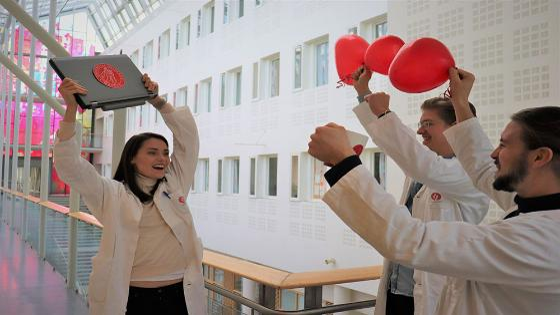 tre glade medisinstudenter som holder hjerteballonger