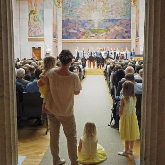 Mor og to barn ser på avslutningsseremonien